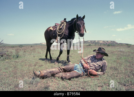 A ranch cowboy takes a rest after lunch on a hot day on a large cattle ranch on the plains of west Texas - Stock Photo