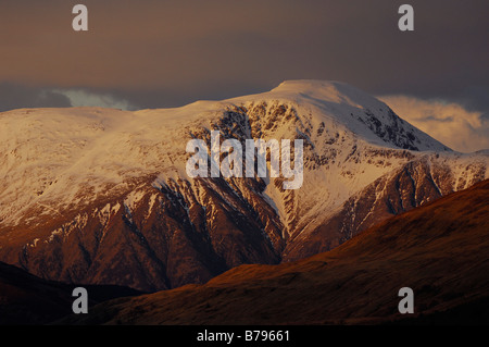 Ben Nevis Scotland s highest mountain rises above dark foothills seen from Ardgour western Scotland UK - Stock Photo