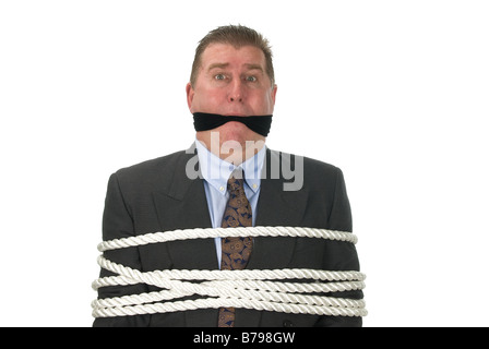 A businessman is tied up by angry co workers - Stock Photo