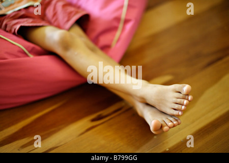 Six year old boy sits in pink beanbag and watches tv - Stock Photo