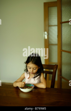 Five year old girl sits at a wooden table and eats a bowl of cereal - Stock Photo