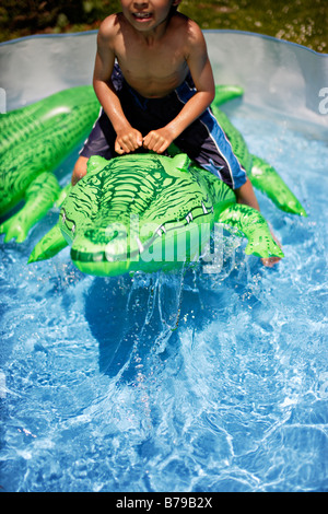 ... Children Ride Inflatable Crocodile In Paddling Pool   Stock Photo
