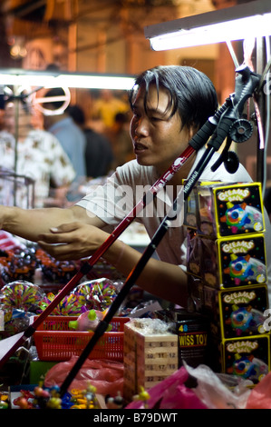 Malaysian man selling toys under neon lights in Melaka street market, Malaysia - Stock Photo