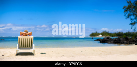 Young woman relaxing on tropical white sand beach - Stock Photo