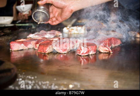 Grilling scotch fillets on the hot plate in the Japanese teppanyaki restaurant. - Stock Photo