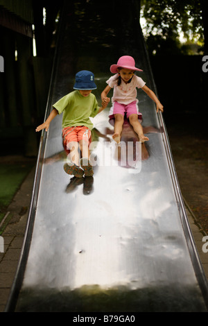 Brother aged six and sister five on wide slide - Stock Photo