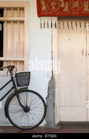 Bike with carry basket leaning against a wall outside a house in Georgetown, Penang, Malaysia - Stock Photo