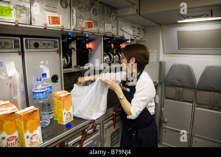 Member of cabin crew working / tidying in the galley on a Gulf Air Airbus A330 aircraft during flight (Bahrain / - Stock Photo