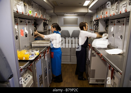 Two members of cabin crew working / tidying in the galley on Gulf Air Airbus A330 aircraft during flight to Bahrain - Stock Photo