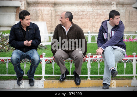 Three men sit by the Statue of the Republic in Taksim Square, Istanbul, Turkey. - Stock Photo