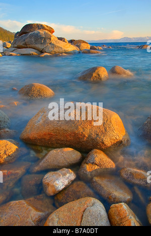 HDR tonemapped Rocks and moving water at sunset on the east shore of Lake Tahoe in Nevada - Stock Photo