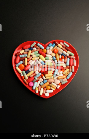 Tablets on a heart made of ceramic - Stock Photo