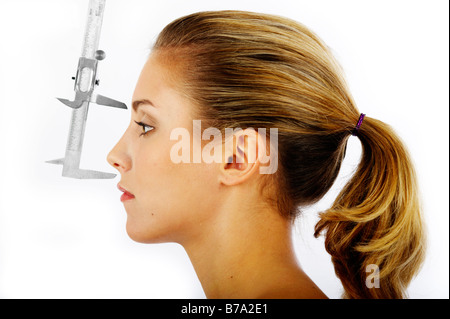 Young woman, distance between the forehead and the nose being measured with a caliper rule - Stock Photo