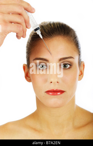Young woman getting an injection against forehead wrinkles - Stock Photo