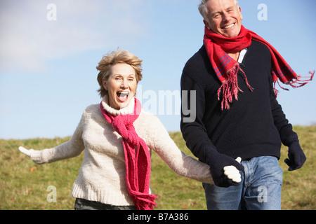 Senior Couple Running In The Park - Stock Photo