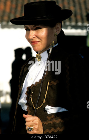 A woman in dressed in decorative equestrian attire at the annual Golegã horse festival in Portugal - Stock Photo