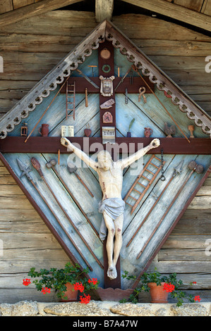 Jesus Christ on a wooden cross, hanging on a wall in the open air musuem of the Bavarian Forest in Tittling, Bavaria, - Stock Photo