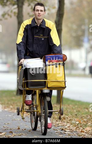 Mailman of the Deutsche Post AG, German post, on a bike in Regensburg, Bavaria, Germany, Europe - Stock Photo