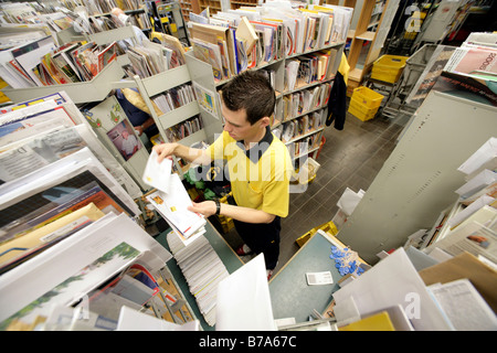 Employee, mailman, of the Deutsche Post AG, German post, sorting his mail in the Regensburg delivery post, Bavaria, - Stock Photo