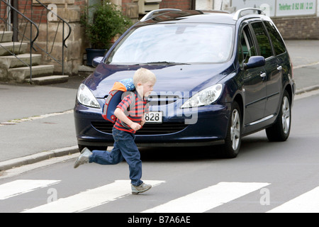 Schoolchild running over a pedestrian crossing while a car is waiting, Bayreuth, Bavaria, Germany, Europe - Stock Photo
