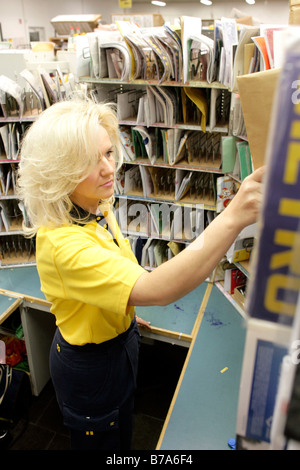 Employee, mailwoman, of the Deutsche Post AG, German post, sorting her mail in the Regensburg delivery post, Bavaria, - Stock Photo