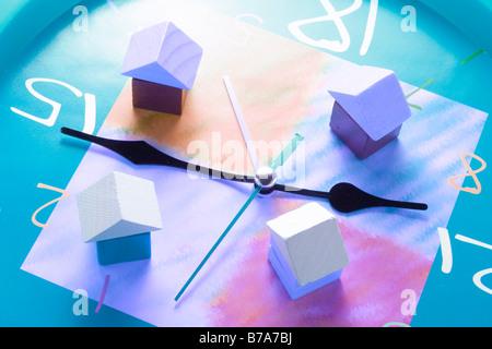 Miniature houses on clock - Stock Photo