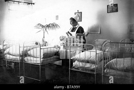 Historical photo, nurse and baby in the hospital, ca. 1910 - Stock Photo