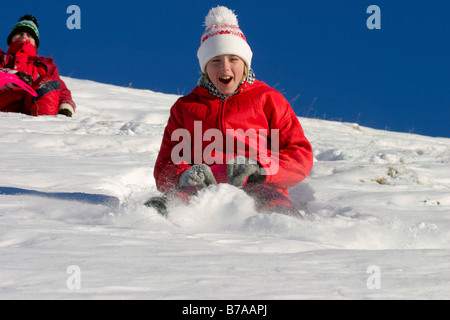 Two girls, 9 and 12 years old, riding on snow-sliders, Dolomites, Italy, Europe - Stock Photo