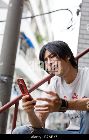 Young man playing a game on a mobile phone, Tokyo, Japan, Asia - Stock Photo