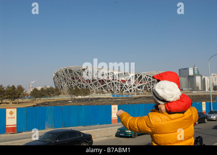 People looking at the Beijing National Stadium Construction site of 2008 Beijing Olympics - Stock Photo