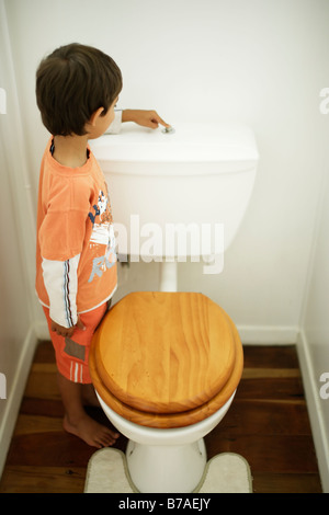 Six year old boy flushes toilet - Stock Photo