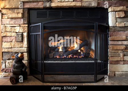 A gas log fireplace provides both emotional and physical warmth as the afternoon sun streams in on a cold winter - Stock Photo