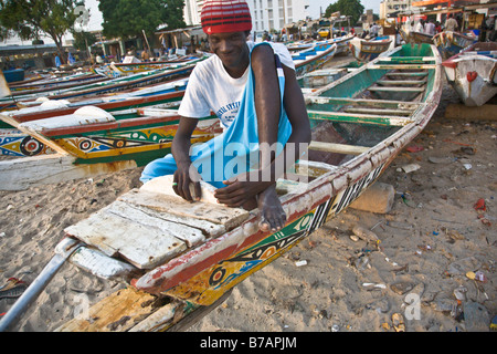 A man sits on one of the colorfully painted fishing boats that line the beach at this fish market in Dakar, Senegal. - Stock Photo
