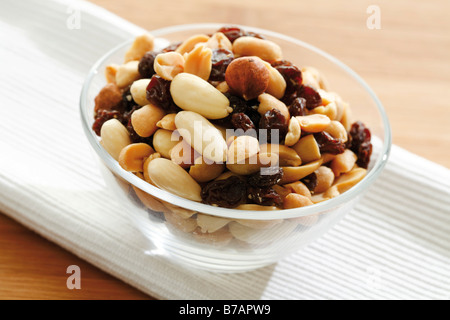 Trail mix, various nuts with raisins, in a glass bowl on a wooden table - Stock Photo