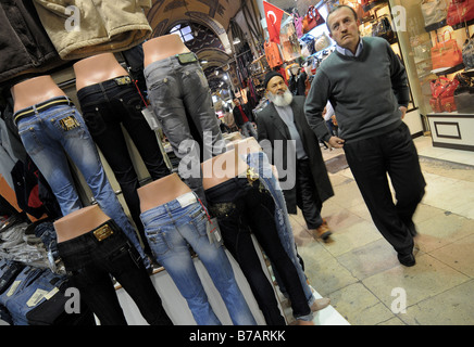 Two local men walk past a stall selling jeans in the Grand Bazaar (Kapali Carsi) in Istanbul, Turkey. - Stock Photo