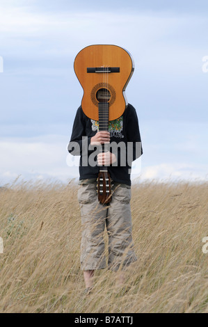 Boy Holding Guitar in Field - Stock Photo