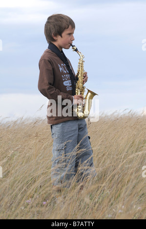 Boy Playing Saxophone in Field - Stock Photo
