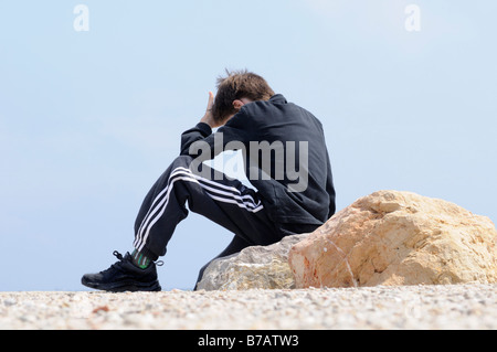 Boy Sitting on Rocks by Coast - Stock Photo