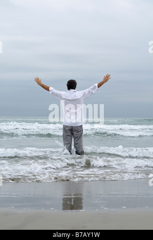 Man Standing in Waves on Beach