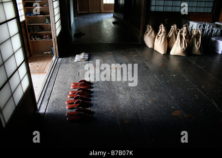 Japanese indoor slippers lined up by sliding doors at the entrance to a temple in Koya-san, Japan - Stock Photo