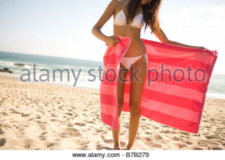 Asian woman in bikini on beach wrapping towel around waist - Stock Photo
