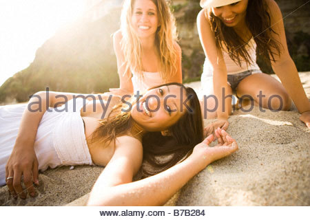 Multi-ethnic friends laying on beach - Stock Photo