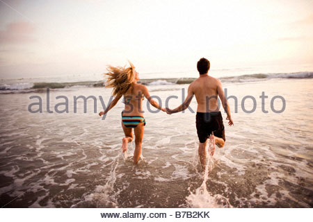 Couple holding hands and running through surf - Stock Photo