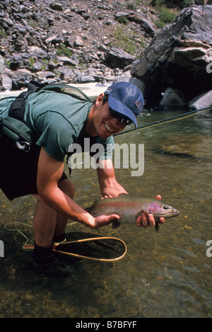 a man holds a large rainbow trout caught while fly fishing the gunnison river in the black canyon national park - Stock Photo