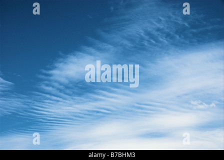 Soft white cloud pattern against a bright blue sky - Stock Photo