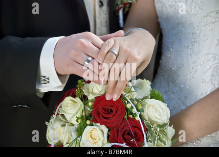the bride and the groom showing their rings above the brides bouquet - Stock Photo