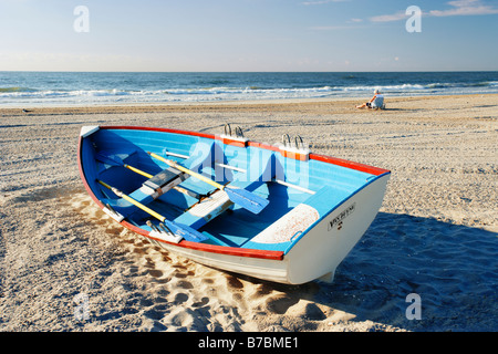 Mature man in background sitting on beach and small boat, New Jersy, USA - Stock Photo