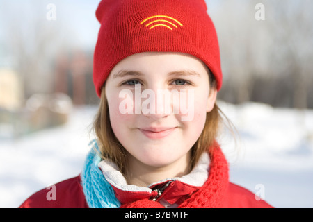 Portrait of 13 year-old girl with red woolen hat outdoor in winter, Winnipeg, Canada - Stock Photo