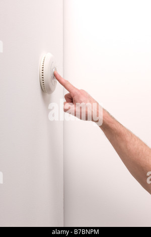 Man testing a domestic fire alarm is working correctly - Stock Photo