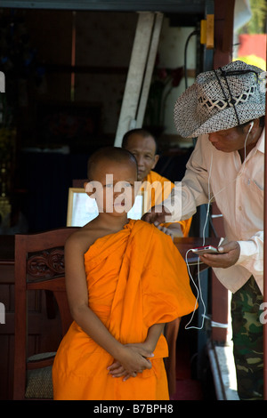A tourist listening to an ipod is talking a young novice Buddhist monk